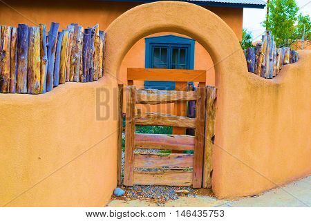 Adobe style rustic building with a gate taken in Taos, NM