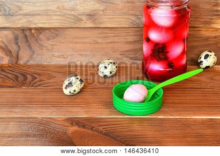 Pickled peeled hard-boiled quail eggs, stained pink by grated beet