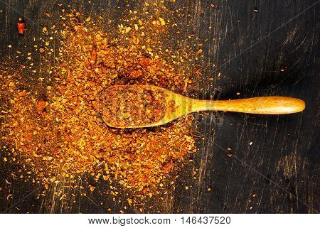 Seasoning. A mixture of hot spices for cooking, with a wooden spoon for spices on a black wooden table. top view, copy space