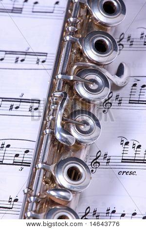 Instrumento de la flauta de plata descansando sobre una partitura