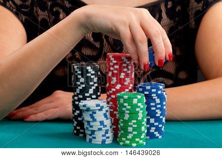 Woman holding gambling chips on green background. Focus on hand holding several blue chips