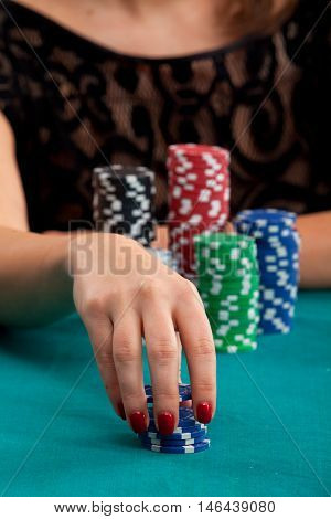 Woman holding gambling chips on green background and placing a bet