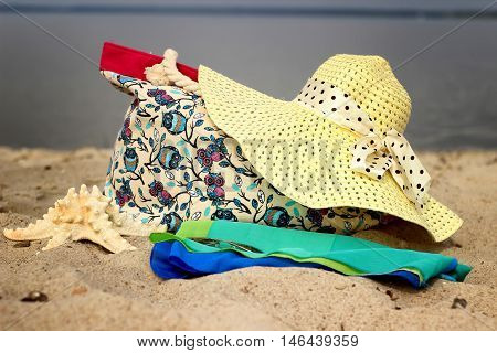 Straw hat, beach bags, sarong, glasses, starfish close-up lying on the sea background.