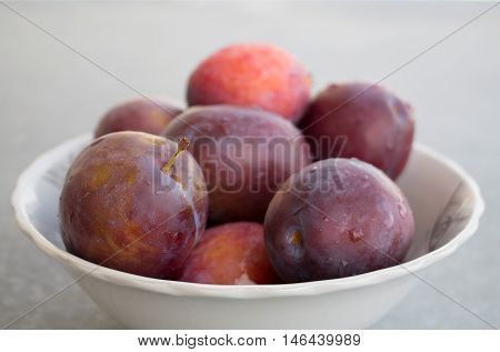Fresh just washed plums in a bowl. Plums with drops