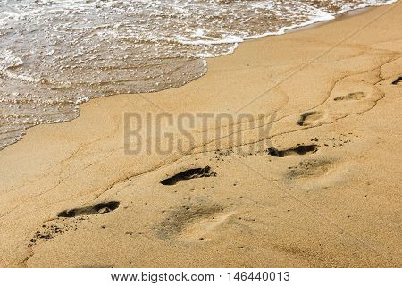 The evening waves of the lake Baikal gradually wash away the traces left in the sand by an unknown girl.