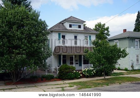 PETOSKEY, MICHIGAN / UNITED STATES - AUGUST 5, 2016: An elegant Victorian home, with a wraparound front porch a balcony, and a white picket fence, near downtown Petoskey.