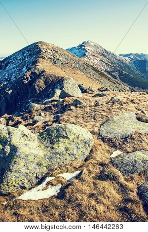 Footpath leading up the peak Dumbier Low Tatras Slovak republic. Hiking theme. Mountains scene. Retro photo filter. Stones snow and dry grass.
