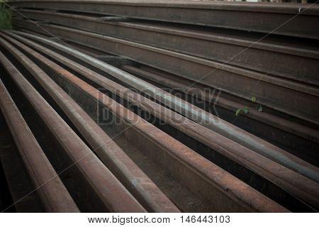 Steel tracks piled together beside the tracks