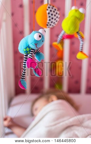 Baby bed with mobile toy above it; baby sleeping