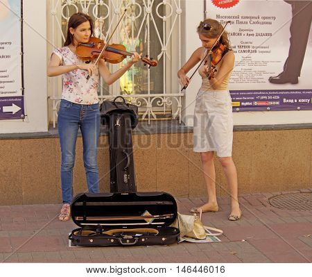 MOSCOW, RUSSIA - August 28, 2016: Two young women street musicians playing violins on the street sidewalk. August 28, 2016 in Moscow, Russia
