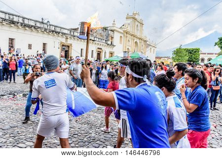 Antigua Guatemala - September 14 2015: Locals run with lit torch in front of cathedral during Guatemalan Independence Day celebrations