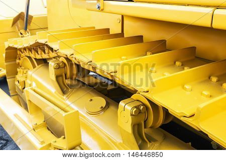 metal tracks on the tractor. yellow tracks tractor. Focus on tractor tracks