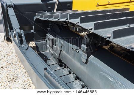 gray tracks on a yellow excavator. focus on excavator tracks