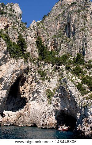 CAPRI, ITALY, MAY 11, 2012:  Small motorboat with tourists goes near coastal rocks near small cave of Capri island