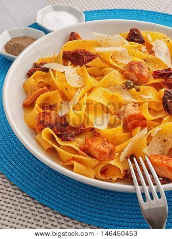 Italian Pasta - fettuccine with dried tomatoes baked salmon and parmesan cheese. Vertical shot