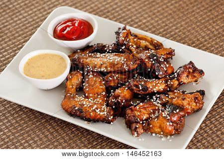 Baked chicken wings with barbecue sauce sesame seeds mustard and catchup. Horizontal shot with beer on background