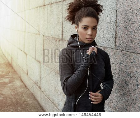 Young beautiful woman in sportswear with earphones on city street