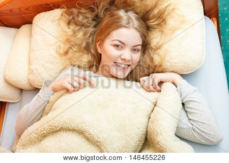 Woman waking up in bed in the morning after sleeping. Young girl laying under wool blanket.