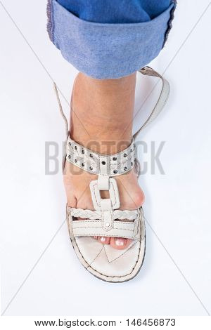 female foot with the bunion of footwear summer shoes on a white background