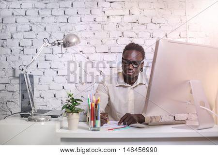 Businessman sitting behind is desk