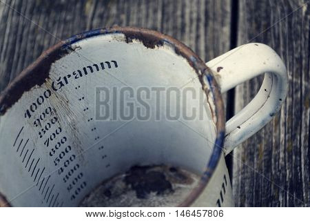 Old Vintage Metallic Cup For 1000 Grams On Wooden Background