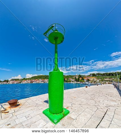 Green beakon at the end of a pier in the Prvic Luka port in Croatia.