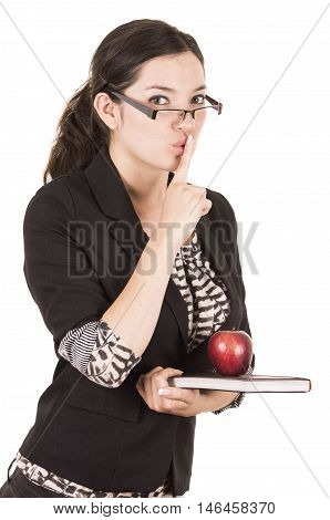 sweet female teacher holding red apple gesturing silence isolated on white