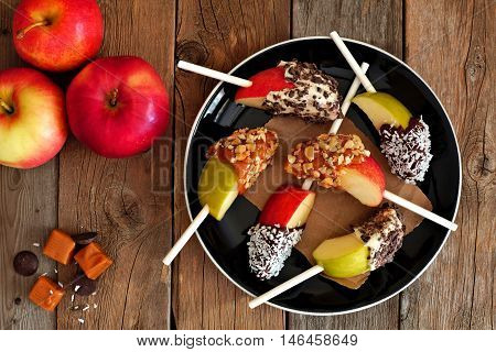 Plate Of Mixed Sweet Caramel And Chocolate Dipped Apple Slices, Overhead Scene On Rustic Wood