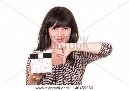 beautiful young disappointed girl holding thumb down and carrying present wrapped in a box isolated on white