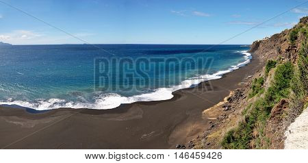 Black Sand Beach With Blue Waters