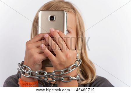 Young girl shackled with a chain using smartphone holding it in front of her face.