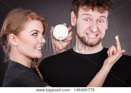 Protection and skincare. Stubborn girlfriend trying to apply cream on her boyfriend face. Man in uncomfortable situation with overprotective woman.