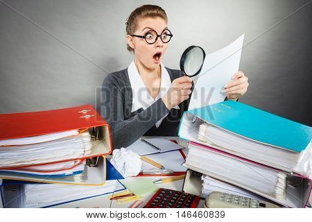 Bureau book keeping workaholism error concept. Shocked secretary examining documents. Female office worker holding paper magnifying glass expressing shock disbelief.