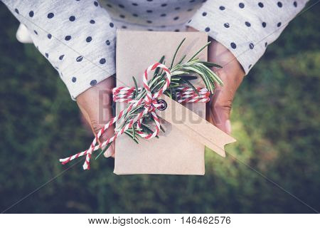 kid holding eco gift box with brown tag holidays toning background