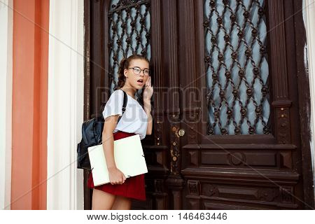 Surprised young beautiful female student standing near door, holding folders, eavesdroping outside.