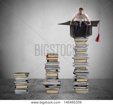 Businessman sitting on a pile of books with graduation cap