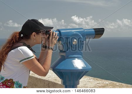 woman using a panoramic telescope looking at the sea