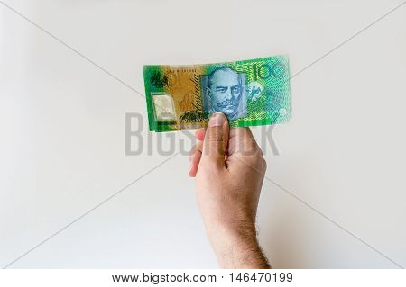 Man holding hundred Australian Dollar banknote in his hands