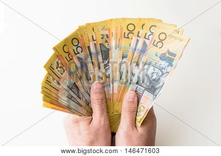 Man holding a bunch of fifty Australian Dollars in his hands