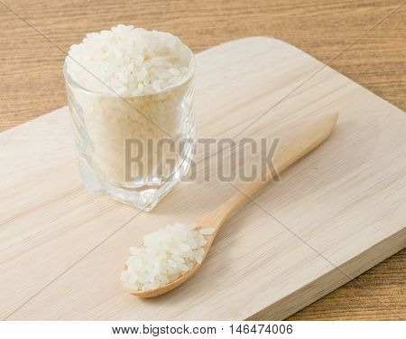 Japanese Cuisine Raw and Uncooked Japanese Rice in A Wooden Spoon and A Glass Cup.