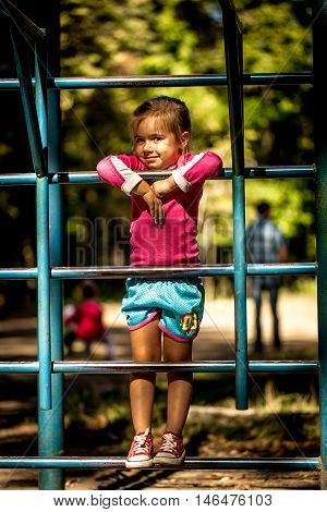 Beautiful Little Girl Playing On Children's Sports Trainers Climbs The Stairs