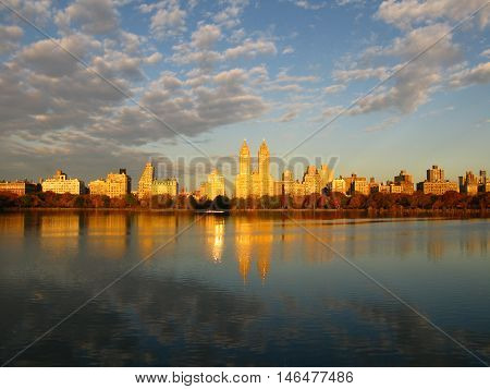 Jackie Kennedy Onassis Reservoir in Central Park, Manhattan, New York. In the background, skyscrapers illuminated by the sun. Photo taken early in the morning at sunrise.