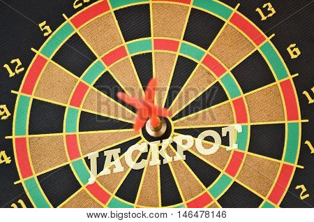 Word Jackpot written on the circular target with a plastic feather in the center