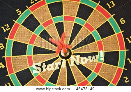 Text Start Now written on the circular target with a plastic feather in the center