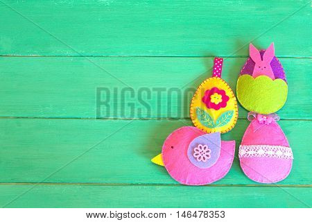 Decorative Easter felt eggs and bird on green wooden background with copy space. Easter background