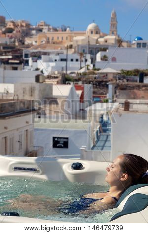 Young woman enjoying outside jacuzzi. In background - the center of Fira Santorini. Vertical shot