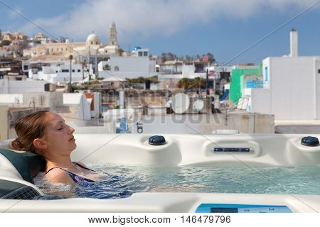 Young woman enjoying jacuzzi outdoors. In background - the center of Fira Santorini