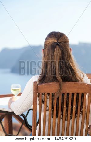Woman with white wine in Oia Santorini. Looking at the caldera. Vertical shot