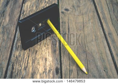 Old audiotape and pencil on wooden background
