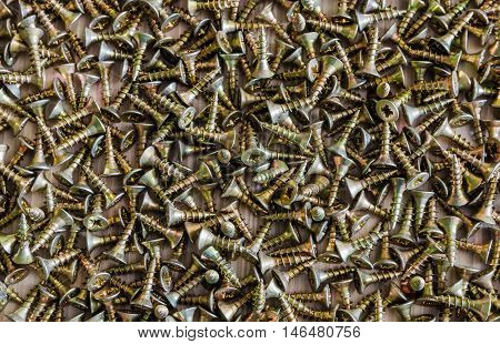 Background from a variety of yellow screws closeup
